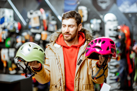 Man in winter jacket choosing mountaineer equipment holding helmets for hiking in the sports shop 写真素材