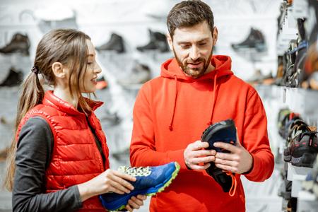 Mam en vrouw in rode sportkleding die trailschoenen kiezen om te wandelen in de buurt van de showacase van de moderne sportwinkel