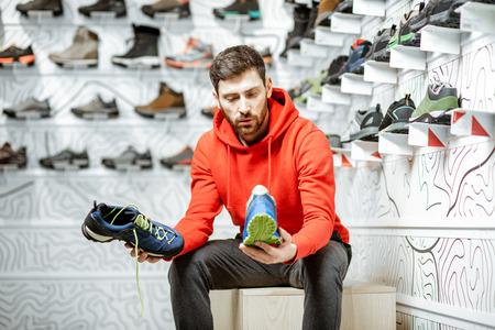 Mann, der Wanderschuhe zum Wandern in der Umkleidekabine des modernen Sportgeschäfts wählt Standard-Bild
