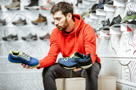 Man choosing trail shoes for hiking sitting in the fitting room of the modern sports shop Stock fotó - 115281292