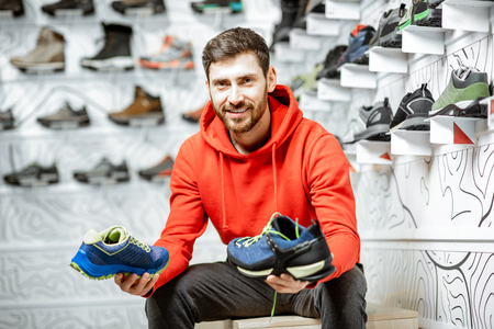 Portrait of a man in the fitting room of the modern sports shop choosing trail shoes for hiking