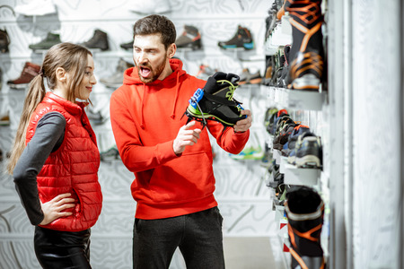 Man and woman looking on the studded shoes for hiking on the ice standing in the modern sports shop Stock Photo