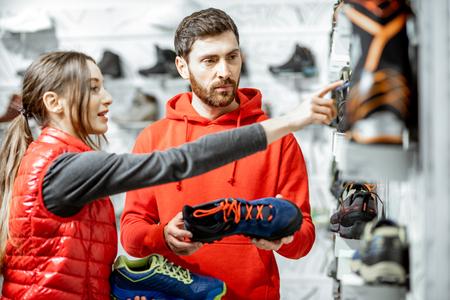 Mam et femme en vêtements de sport rouges choisissant des chaussures de randonnée pour la randonnée debout près de la vitrine du magasin de sport moderne