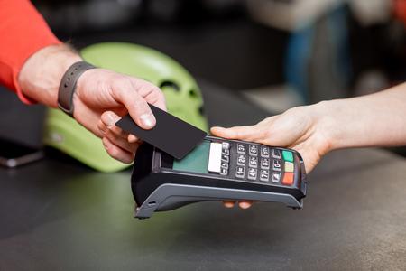 Mann, der mit Bankkarte und Registrierkasse am Schalter des Sportgeschäfts kauft, Nahaufnahme