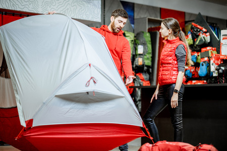 Salesman selling camping equipment to a young woman client in the sport shop