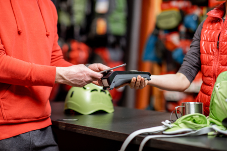 Man making purchase with smart phone and cash register at the counter of the sports shop Stock Photo