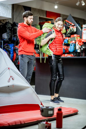 Salesman selling travel equipment to a young woman client trying a backpack in the sports shop