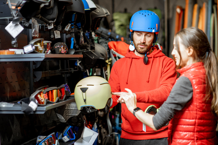 Man and woman choosing protective helmet for riding or mountain hiking in the shop with sports goods
