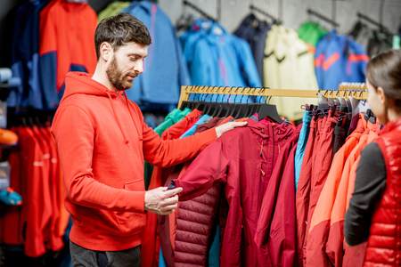 Man choosing winter clothes picking up down jackets on the hanger in the sports shop