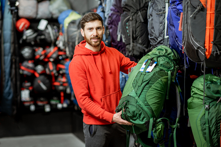 Man choosing some sports equipment looking on the backpacks for traveling in the sports shop