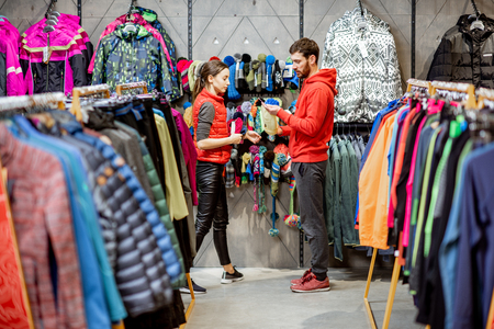 Man and woman looking for winter clothes standing together in the sports shop with colorful jackets and garment