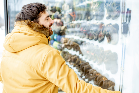 Man in winter jacket hugging showcase of the shop with sports footwear