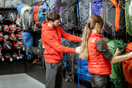 Couple choosing sports equipment looking on the backpacks for traveling in the shop