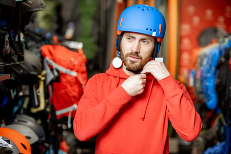 Man choosing protective helmet for riding or mountain hiking in the shop with sports goods