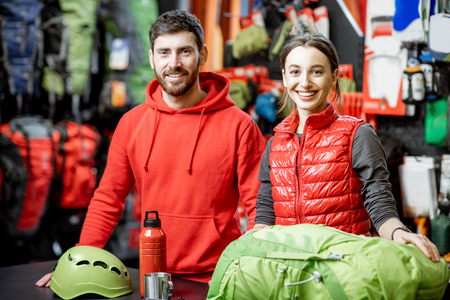 Portrait of a happy sales man and woman standing on the cash register of the sports shop with travel equipment and clothes on the background Reklamní fotografie