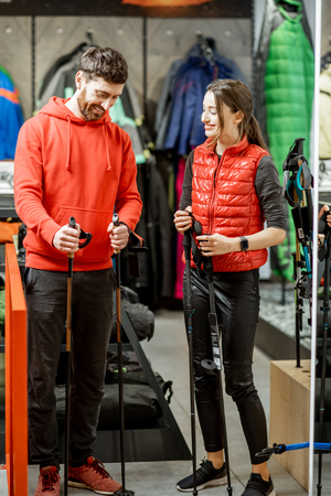 Man and woman choosing traveling equipment looking on the hiking sticks in the shop