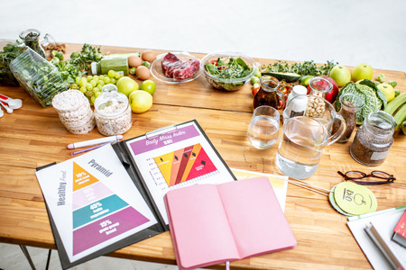 Nutritionists working place with drawings on the topic of healthy eating, empty notebook and different products on the table Stockfoto