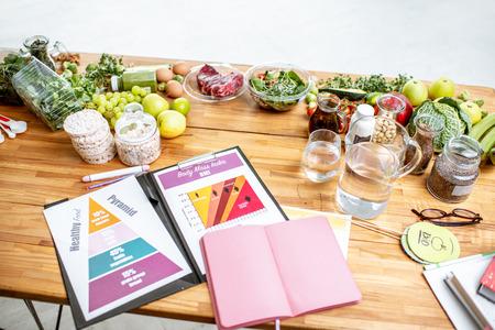 Posto di lavoro di nutrizionisti con disegni sul tema del mangiare sano, quaderno vuoto e diversi prodotti sul tavolo
