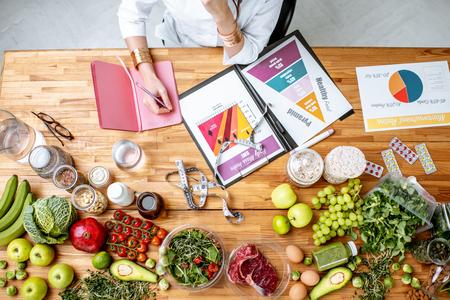 Dietetyk pisze plan diety, widok z góry na stole z różnymi zdrowymi produktami i rysunkami na temat zdrowego odżywiania Zdjęcie Seryjne