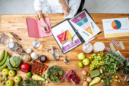 Dietitian writing diet plan, view from above on the table with different healthy products and drawings on the topic of healthy eating Banco de Imagens - 115514535