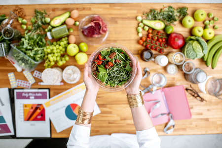 Dietitian holding cooked salad above the table full of various healthy products and drawings on the topic of healthy eating Reklamní fotografie