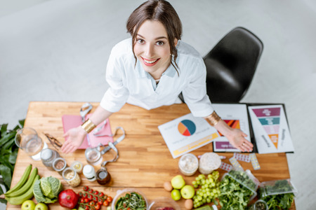Portrait of a young woman nutritionist in medical uniform standing near the table full of various healthy products indoors Archivio Fotografico