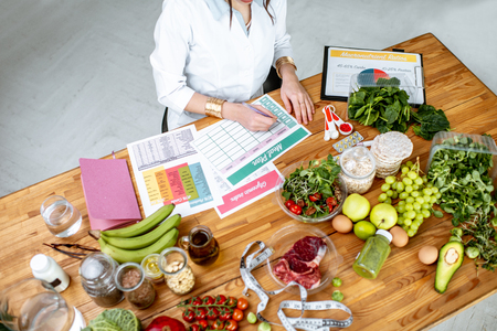 Dietitian writing a diet plan, view from above on the table with different healthy products and drawings on the topic of healthy eating Stock Photo