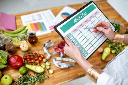 Dietista escribiendo un plan de dieta, vista desde arriba en la mesa con diferentes productos saludables y dibujos sobre el tema de la alimentación saludable Foto de archivo