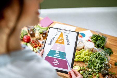 Holding schematic meal plan for diet with various healthy products on the background
