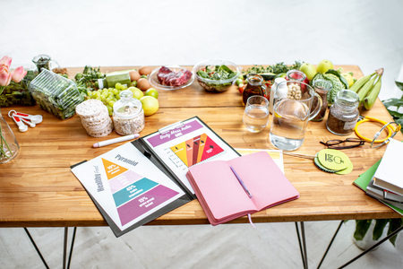 Nutritionists working place with drawings on the topic of healthy eating, empty notebook and different products on the table Reklamní fotografie