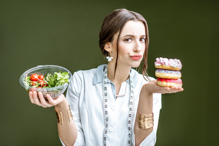 Young woman nutritionist looking on the donuts with sad emotions choosing between salad and unhealthy dessert on the green background