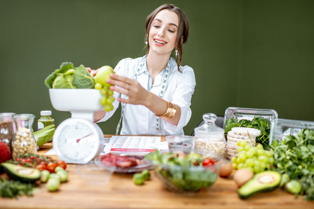 Woman dietitian in medical uniform working on a diet plan weighting fruits sitting with various healthy food ingredients indoors Stock Photo