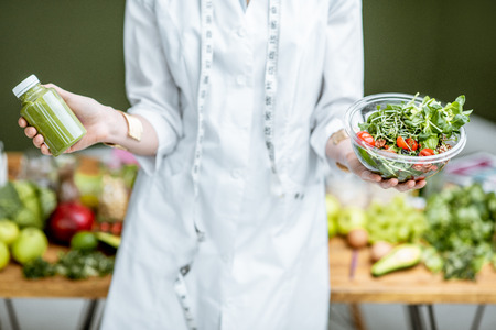 Nutritionist in medical gown holding salad and smoothie drink with healthy food on the background, close-up view with no face Stock Photo