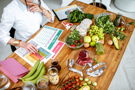Dietetyk piszący plan diety, widok z góry na stole z różnymi zdrowymi produktami i rysunkami na temat zdrowego odżywiania