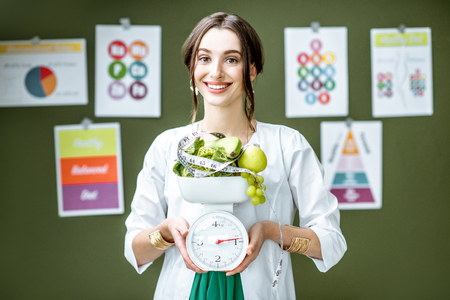 Young woman nutritionist in medical gown holding weights full of healthy products standing on the wall background with diet schemes