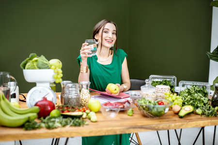 Portrait of a beautiful woman as a dietitian sitting with glass of water and various healthy food ingredients in the green office