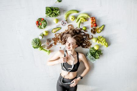 Schoonheidsportret van een sportvrouw omringd door verschillende gezonde voeding die op de vloer ligt. Gezond eten en sport lifestyle concept Stockfoto