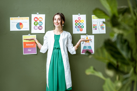 Portrait of a woman dietitian in medical gown standing on the green wall background with drawings on a topic of healthy food indoors