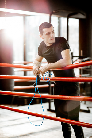 Portrait of a young athletic man in black sportswear standing on the boxxing ring at the gym