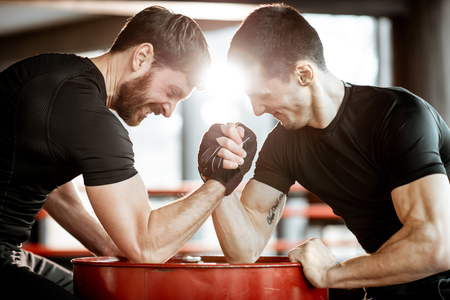 Two young athletes in black sportswear having a hard arm wrestling competition on a red barrel in the gym Standard-Bild - 115897560