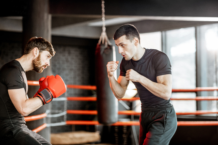 Boxing trainer showing to a man how to fight, teaching to box in the boxing ring at the gym