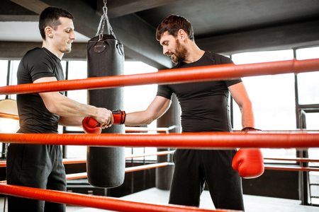 Boxing trainer helping man to relax hand, avoid injuries during the boxing training in the gym