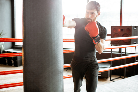 Athletic man in black sportswear training to box with punching bag on the boxing ring at the gym Reklamní fotografie