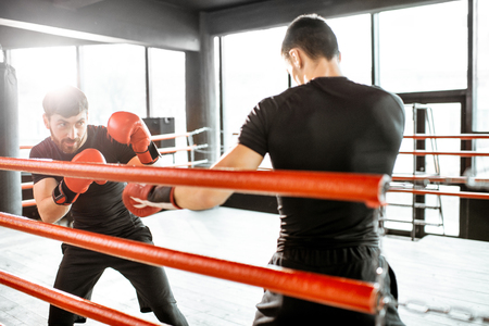 Two professional boxers in black sportswear during the fight on the boxing ring at the gym