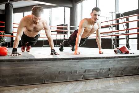 Two athletic men doing push-ups on the boxing ring, training before boxing at the gym Reklamní fotografie