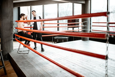 Boxing trainer giving instructions during a break motivating a boxer sitting on the corner of the boxing ring