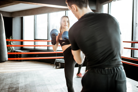 Young woman training to box with personal coach on the boxing ring at the gym