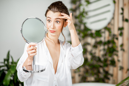 Woman taking care of her skin, worried about acne or aging process in the bathroom. Facial skin care concept 写真素材