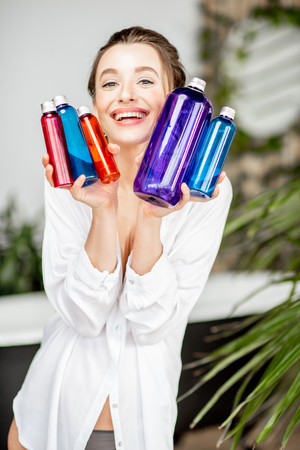 Portrait of a young and happy woman holding lots of colorful bottles with different liquids for self-care in the bathroom Stok Fotoğraf