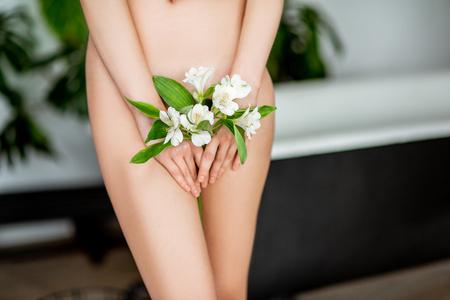 Der Körper einer schönen Frau mit einer Blume, die ihren intimen Platz im Badezimmer bedeckt